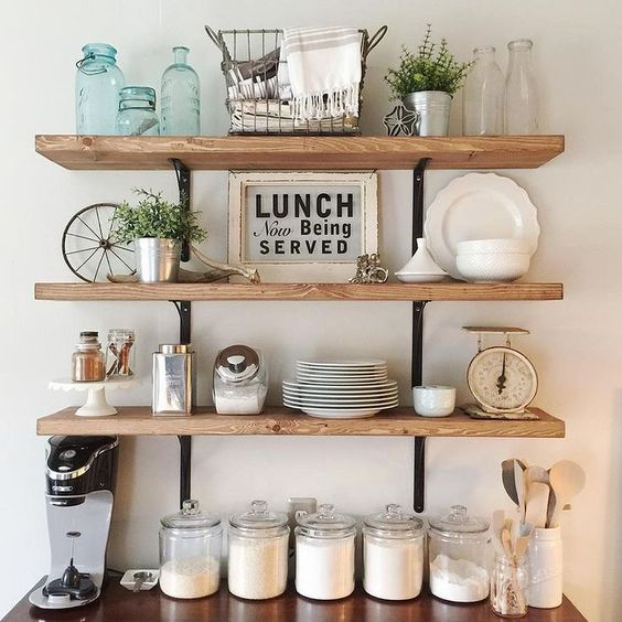 three lines wooden open shelves in the kitchen supported by black metal on the white painted wall.