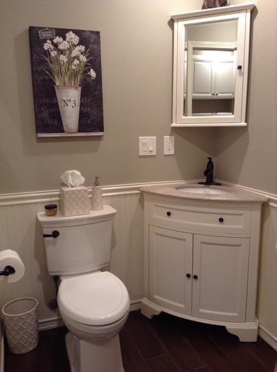 triangular corner vanity with white wooden cabinet, cream marble top, dark faucet, white wooden triangular cabinet with mirror