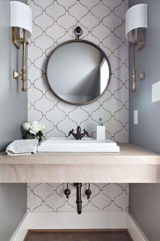 vanity with grey wall, white arabesque tiles on accent wall, marble vanity, white sink, round mirror on the wall, sconces