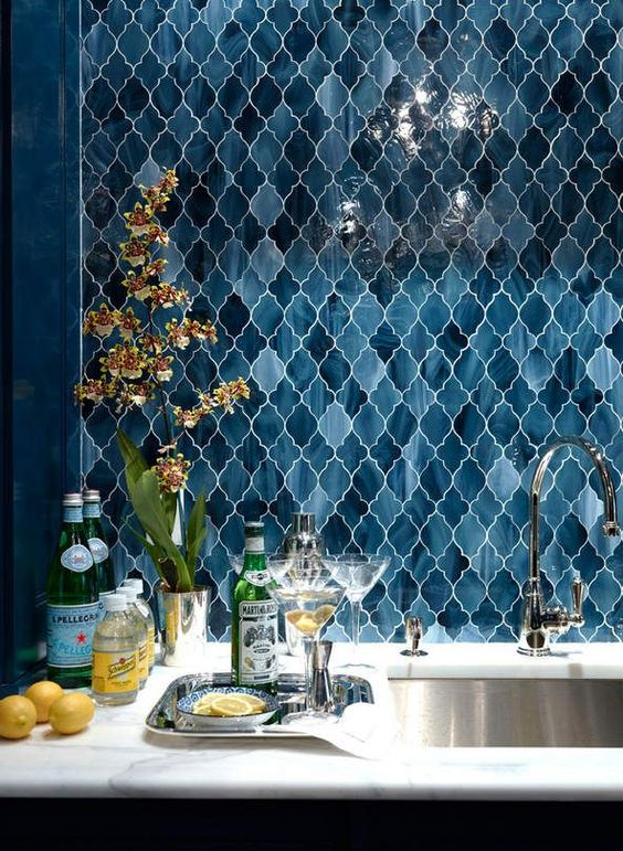 vanity with white marble, silver inside, blue arabesque tiles on the wall