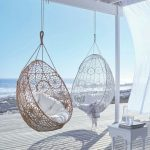 White And Brown Eggshaped Swings On The Balcony With White Wooden Floor, White Coffee Table, White Curtain