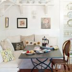 White Dining Nook With Pillows, White One Lined Open Shelf On Top, Black Table, Brown Rattan Chair