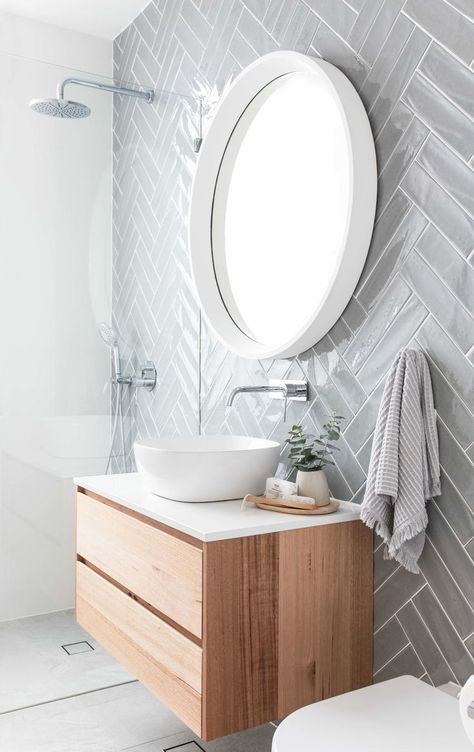 white framed round mirror on the bathroom with grey tiles wall, white sink, brown wooden cabinet