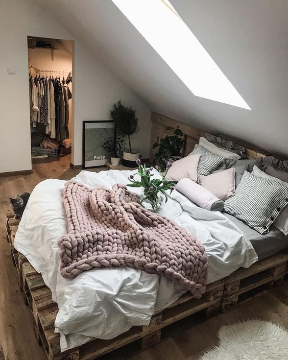white grey bedding with pink woven blanket on wooden platform