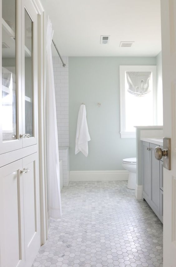 white hexagonal tiles in the bathroom with white furniture, light baby blue wall