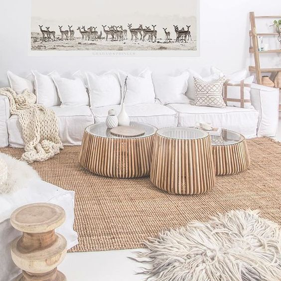 white living room, rattan rug, wooden lattice round table with glass top, white sofa, white wall, white chairs, white pillows