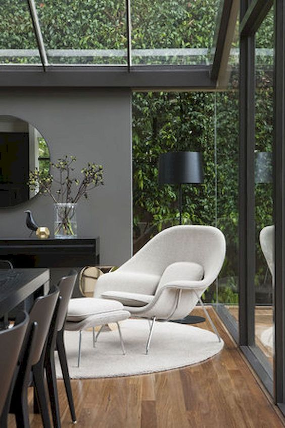 white lounge chair with square ottoman put near the window
