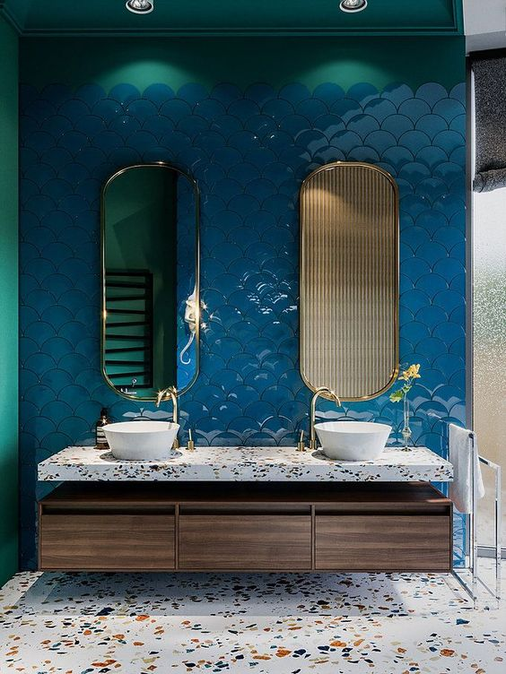 white sink with wooden cabinet, terrazzo counter top, terrazzo flooring, deep blue scale tiles on the wall with gold framed mirrror