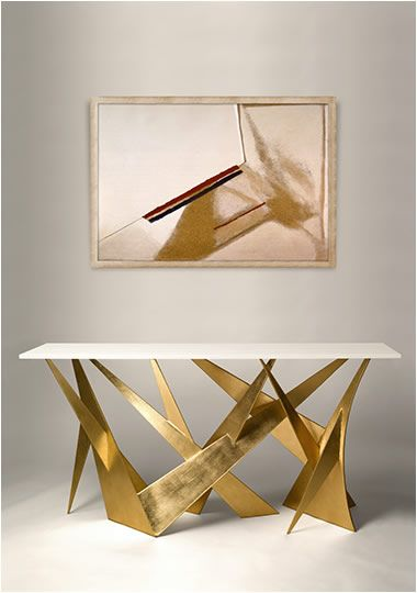 white topped console table with golden abstract metal support under, a picture on the wall