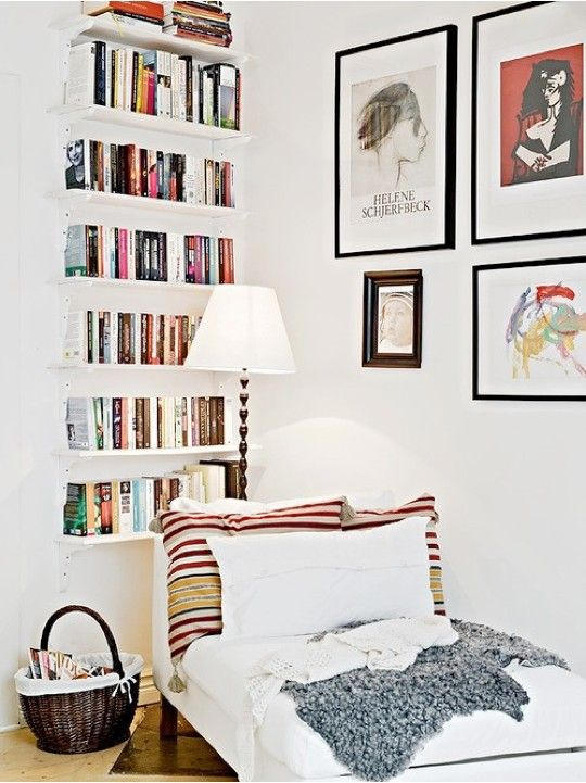 white wall dorner with white wooden floating bookshelves with lounge chair