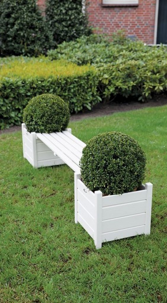 white wooden bench with pots for plants built in on both ends