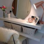 White Wooden Floating Shelves With White Rattan Boxes, Round Frameless Mirror, Lamp, White Chair With Faux Sheep Skin