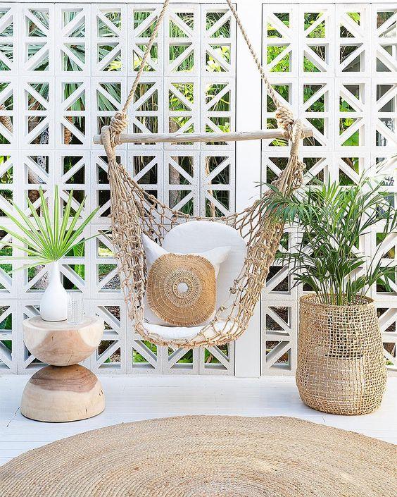 white wooden floor, rattan rug, wooden side table, basket, rattan swing chair