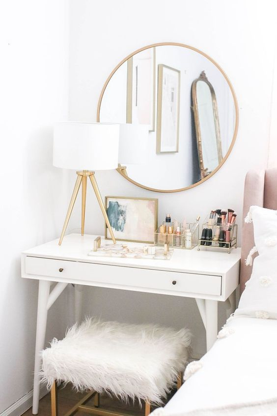 white wooden table with white faux fur cushioned chair, white lamp, golden round mirror