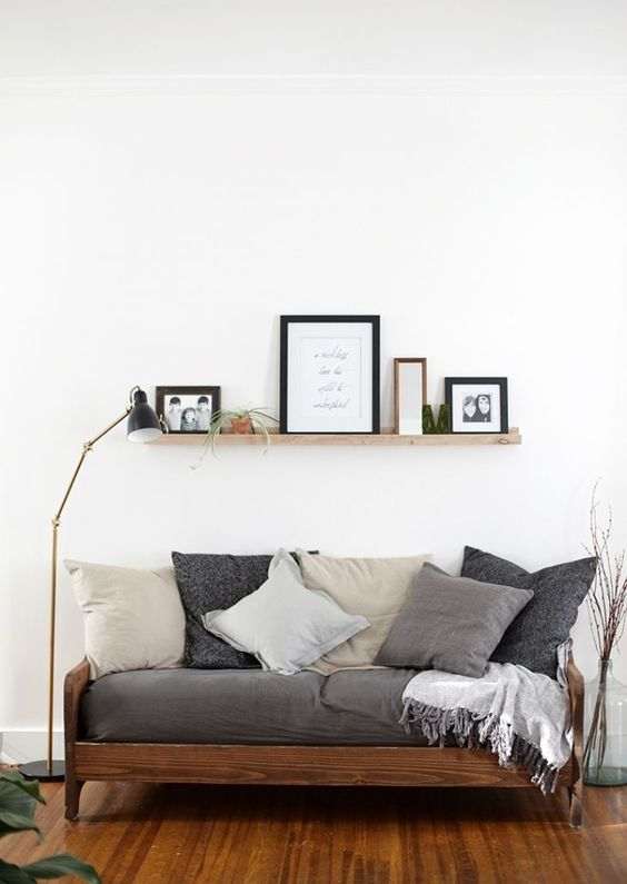 wooden sofa with grey cushion, grey colored pillows