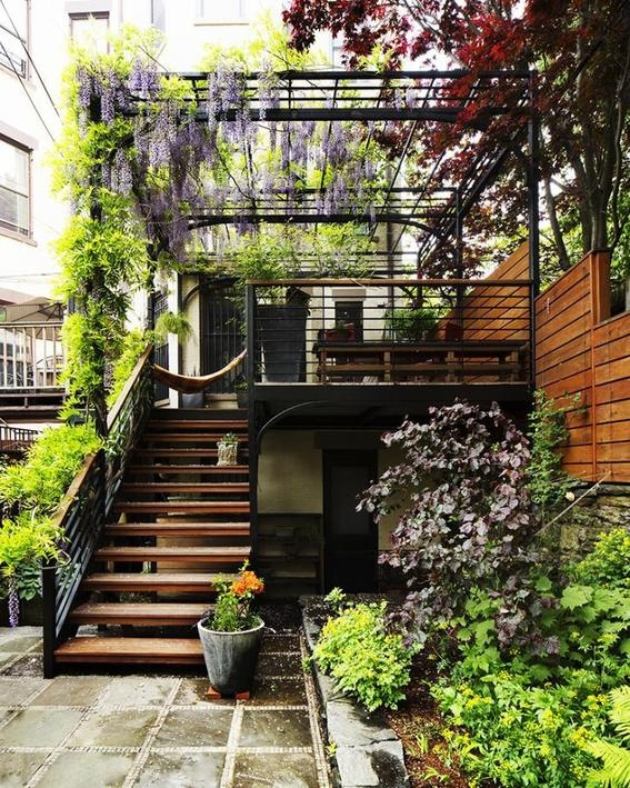 backyard garden with plants on the pergolla, stairs, soil, wooden stairs, wooden wall
