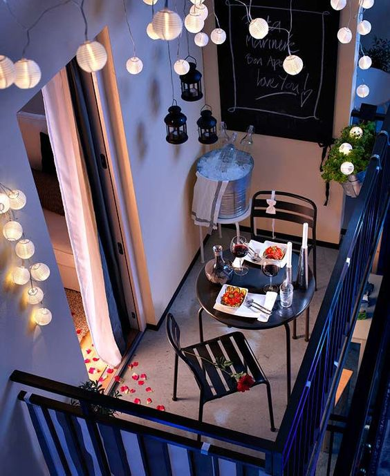 balcony, grey floor, black fence, white wall, wall decoration, black fake pendants, fairy light, round black metal dining set