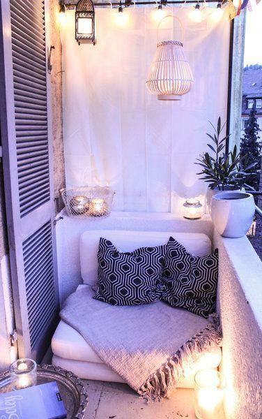 balcony, wooden floor, white low chair, white cloth, candles, lamps on rail, rattan pendant