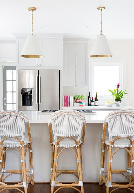 bar stools with white seating on rattan legs, white island, white cover pendants, white cabinet, white kitchen top