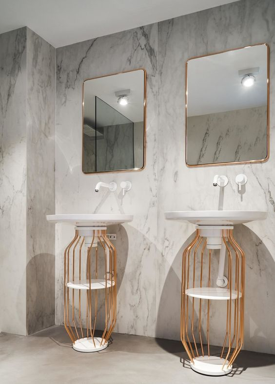 bathroom, beige floor, white marble wall, white sink, golden cage with shelves under the sink, square mirrors with golden frame