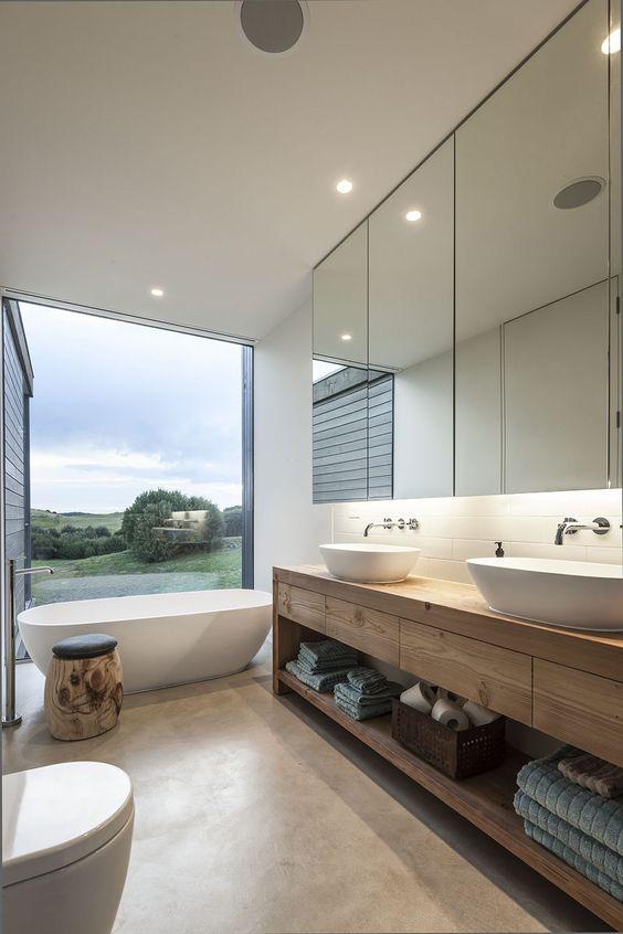 bathroom, beige floor, white tiles backsplash, white wall, wooden vanity with drawers and shelves, white sink, white tub, white toilet, mirror