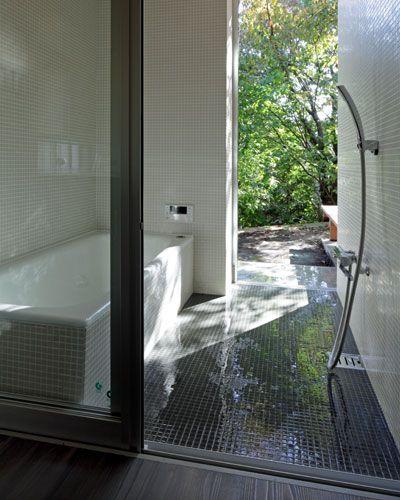 bathroom, black wooden floor, black small floor tiles, white small wall tiles, shower, white tub, open wall