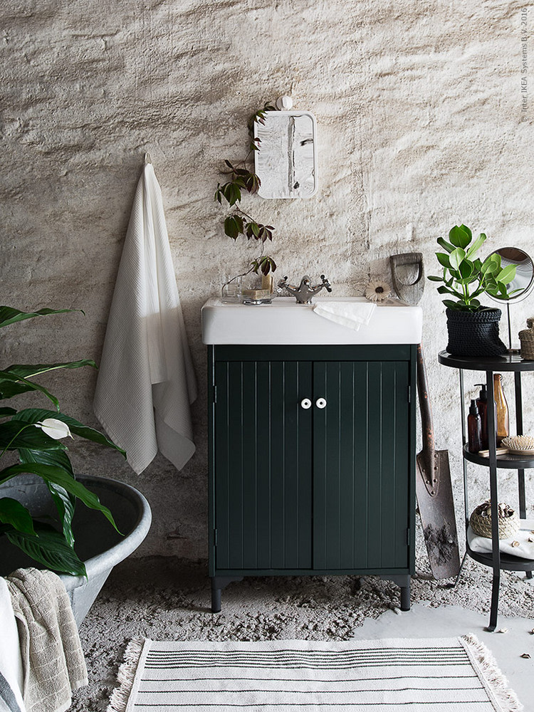 bathroom, cemented floor, white rug, white textured wall, green cabinet with white sink on top, small mirror, small shelves