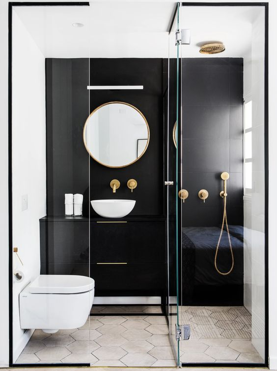 bathroom, geometric floor tiles, white toilet, white sink, round mirror, white painted walls with one black side, black vanity