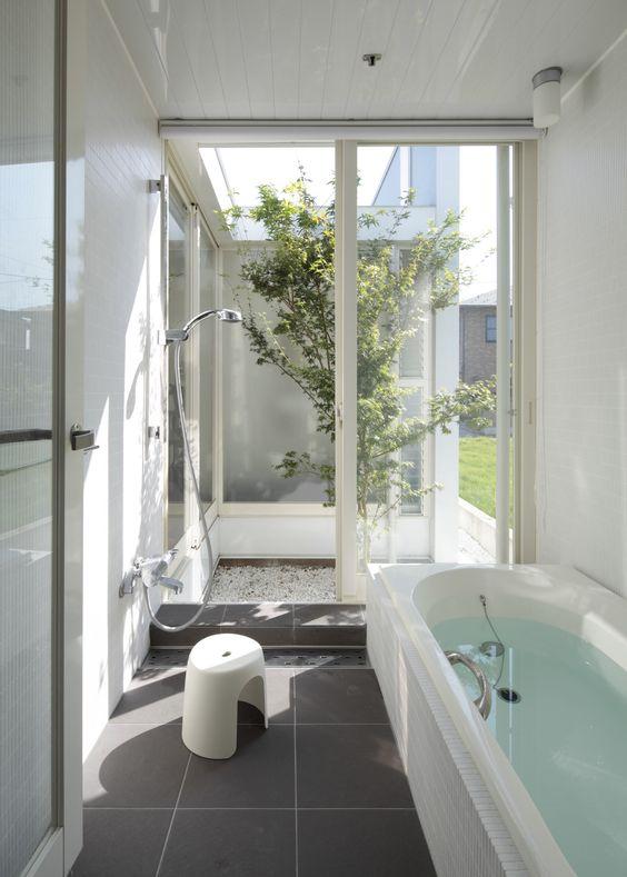 bathroom, grey floor tiles, white wall, white tub, shower, glass sliding door