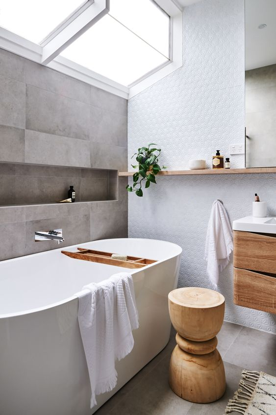 bathroom, grey floor, white rug, white tub, grey wall tiles, white accent wall, wooden floating drawers, white counter top, mirror, floating shelves, glass corner ceiling