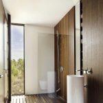 Bathroom, Grey Floor, White Tall Sink, White Toilet, Wooden Floor, Wooden Wall, Shower Area, Door To Outside