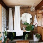 Bathroom, Grey Floor, Wooden Shelves, Black Tub With Clawfoot, Brown Open Brick Wall, White Round Curtain, Plants, Glass Pendant, Wooden Ceiling