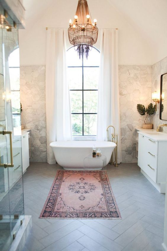 bathroom, grey herringbone floor tiles, warm marble wall, tall window with curtain, white cabinet, mirror, moroccan rug, shower area
