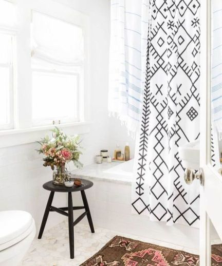 bathroom, marble floor, white wall, window, white shade, white marble tub, black stool, white curtain with pattern, patterned rug