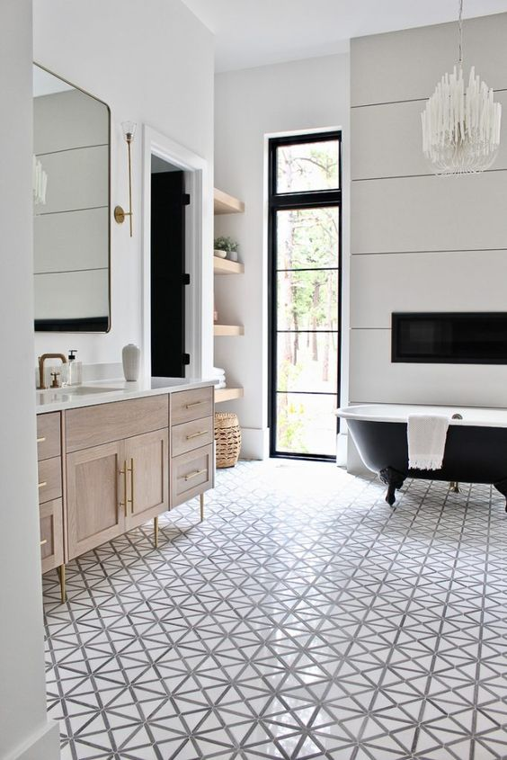 bathroom, patterned floor tiles, white wall, wooden vanity with white top, large mirror, wooden floating shelves, black tub, chandelier