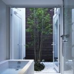 Bathroom, White Floor, White Wall, Shower, White Tiles Tub, Glass Double Door, Small Patio With White River Stones, Tree, Wooden High Fence