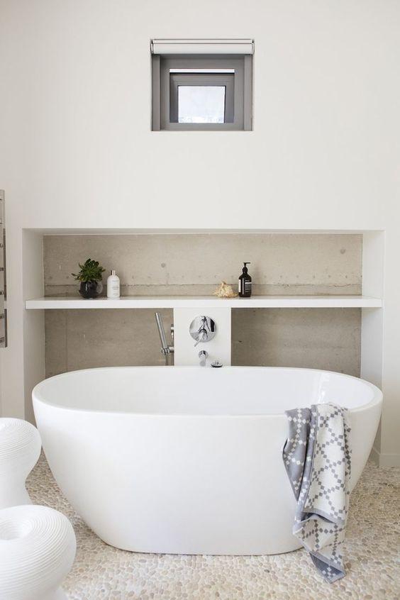 bathroom, white pebbles floor, white wall, built in shelves, white tub, white stool