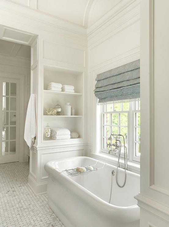 bathroom, white tiny tiles, white tub, white wooden wall with shelves, white framed windows, blue roman shades