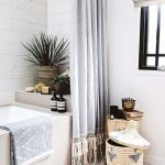 Bathroom, White Wooden Floor, Rattan Baske, Wooden Stool, White Wall, White Open Brick Wall, Grey Curtain With Fringes, Grey Tub, White Shade