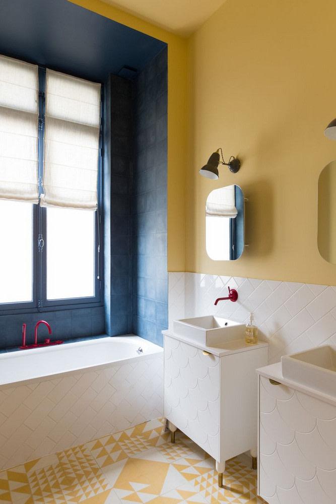 bathroom, white yellow floor tiles, white subway tiles on tub, white fish scale tiles on sink, white subway tilse on backsplash, yellow wall, blue tiles on tub area, red faucet,