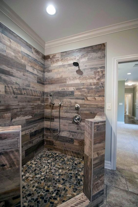 bathroom with black pebbles on the floor, wooden look wall tiles, silver faucet