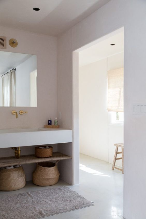 bathroom with floating vanity, floating shelves, square mirror, white wall, arch wall, rattan basket, rug, wooden stool