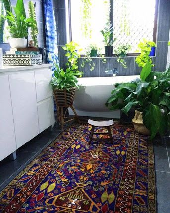 bathroom with grey tiles, rug, white tub, low small stool, glossy white vanity, blue wall tiles, plants on window sil, floor, vanity