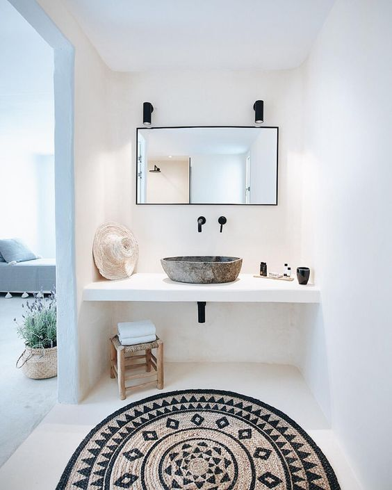 bathroom with white floor, white wall, white floating vanity, grey sink, square mirror, sconces, rattan stool, patterned rattan rug