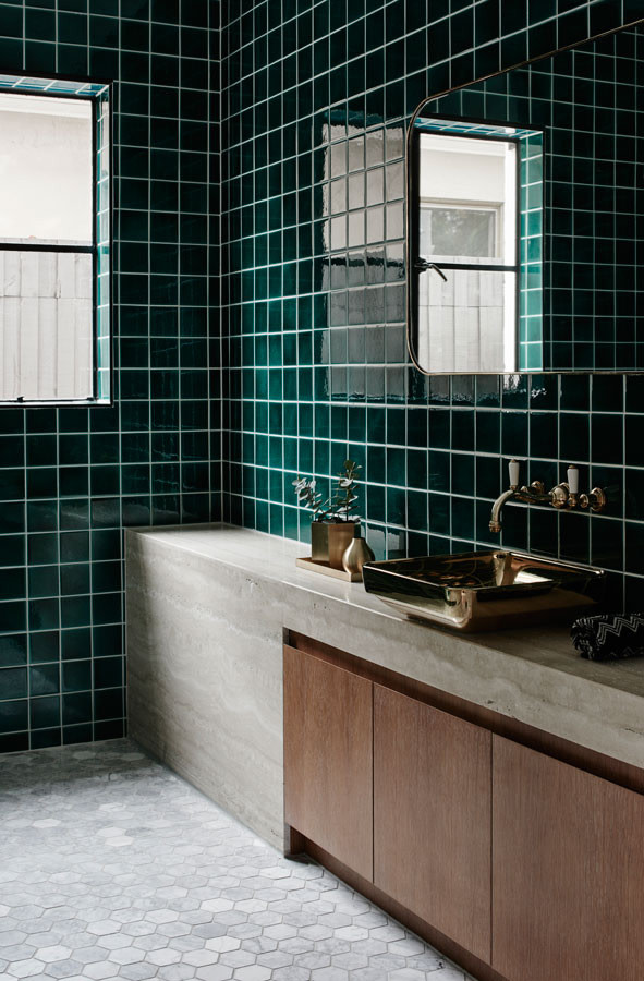 bathroom with white hexagon floor tiles, green square wall tiles, grey marble sink, wooden door, metal sink