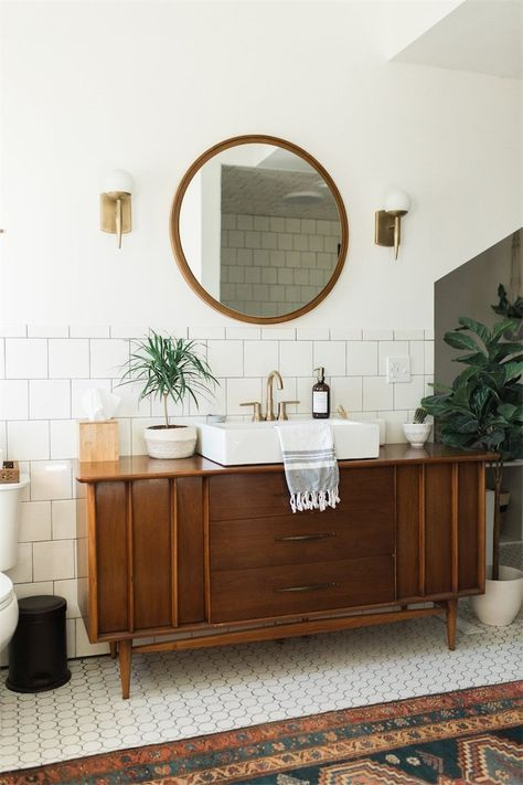 bathroom with white small hexagon tiles, rug, white backsplash wall, white wall, sconces, wooden cabinet, white sink