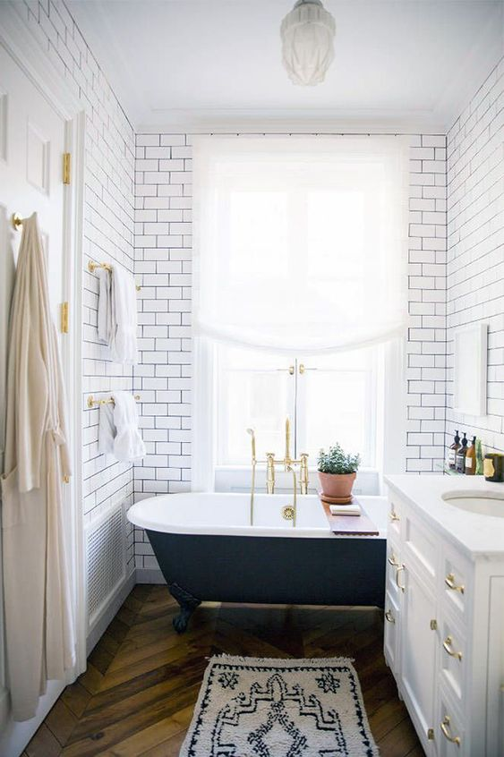bathroom, wooden chevron floor, white subway wall, black clawfoot tub, white vanity, pendant