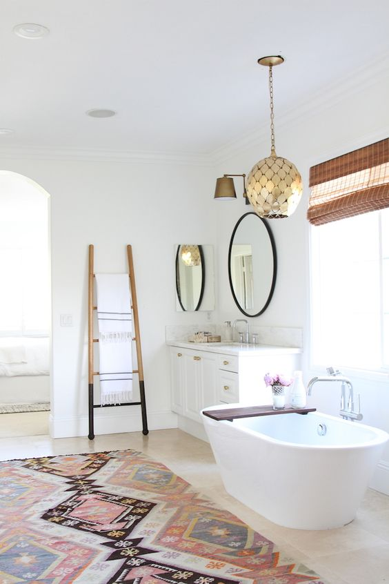 bathroom, wooden floor, geometrical patterned rug, white cabinet, white tub, bamboo stick shade, golden scale pendant,
