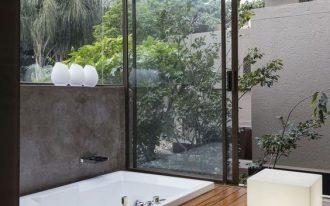 bathroom, wooden planks floor, white tub, glass wall, glass sliding door, white ceiling