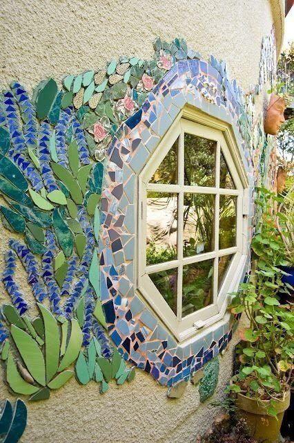 beautiful mural on exterior wall around an octagon window